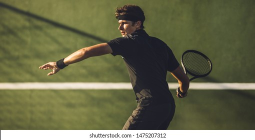 Professional tennis player about to hit a forehand during a game. Tennis player playing on hard court.