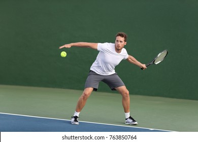 Professional tennis player athlete man hitting forehand ball on hard court playing tennis match. Sport game fitness lifestyle person living an active summer lifestyle.