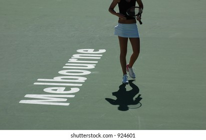 A professional tennis player at the Australian Open over the Melbourne sign on the court.