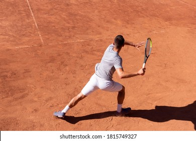 Professional tennis player performs forehand hit on clay tennis court. Young male athlete with tennis racket in action. Junior tennis sport. Back view, shadow, copy space