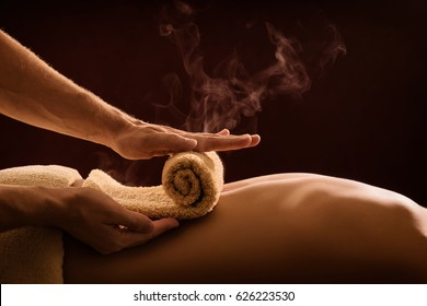 A professional therapist applies a hot towel on the back of a man. Hot towel compress. SPA treatment - Shutterstock ID 626223530