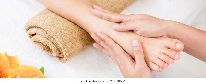 Professional therapist giving relaxing reflexology Thai foot massage treatment to a woman in spa - panoramic banner