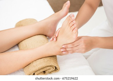 Professional therapist giving relaxing traditional thai reflexology foot massage to a woman in spa