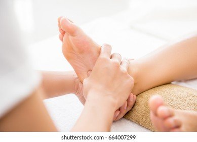 Professional therapist giving traditional thai foot massage to a woman in spa