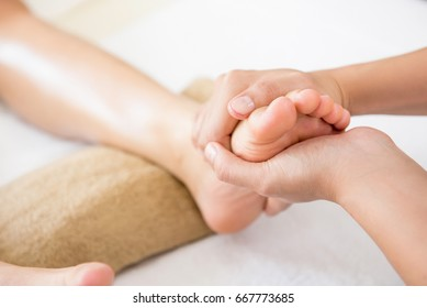 Professional therapist giving traditional thai foot massage to a woman
