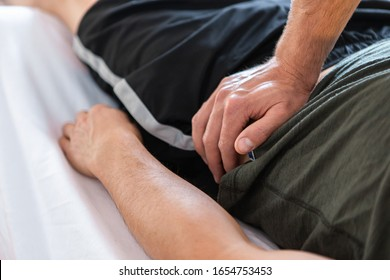 Professional therapist massaging a lying muscular man. Hands of masseur giving treating massage to his client. Body massage therapy