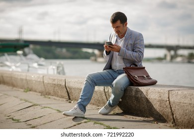 Professional, thoughtful, official business man with a briefcase and a smart phone sitting and texting on a blurred river coast background. A successful business employee working outdoors. Copy space.
