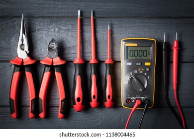 Professional tools for electrician. Screwdrivers, nippers, tester on black wooden background. Studio shot. View from above. Industrial backdrop.