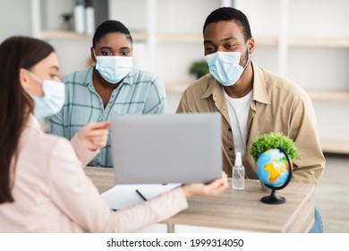 Professional Tour Agent Consulting Customers Couple Showing Laptop Recommending Vacation Destination For Black Spouses Sitting In Travel Agency Office. Selective Focus On Toursits Wearing Face Masks