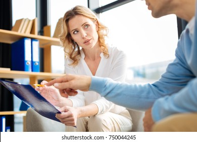 Professional treatment. Nice smart pleasant man pointing at the notes and asking a question to his therapist while having a psychological session