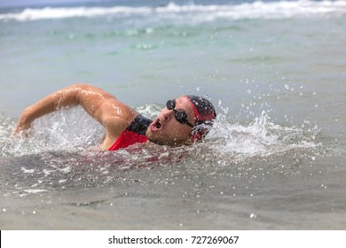 Professional triathlete man swimming crawl ocean freestyle crawl in ocean. Male triathlon swimmer wearing cap, goggles and red triathlon tri suit training for ironman breathing out of water.