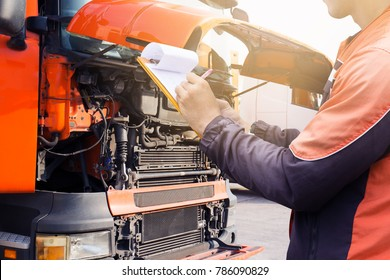Professional truck driver checks list a truck of engine