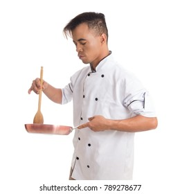 Professional is using a frying pan and wooden spoon. Young chef is in uniform. White background.