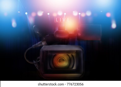 professional video camcorder with set of light hanging in television studio background.