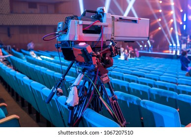 Professional video camera on a tripod with a screen for filming events and TV broadcasting from the concert hall