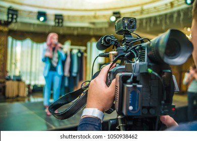 professional video camera. professional operator taking video inside room space. tv camera. film maker. back view.Photographer video recording activity within the event