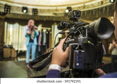 professional video camera. professional operator taking video inside room space. tv camera. film maker. back view.