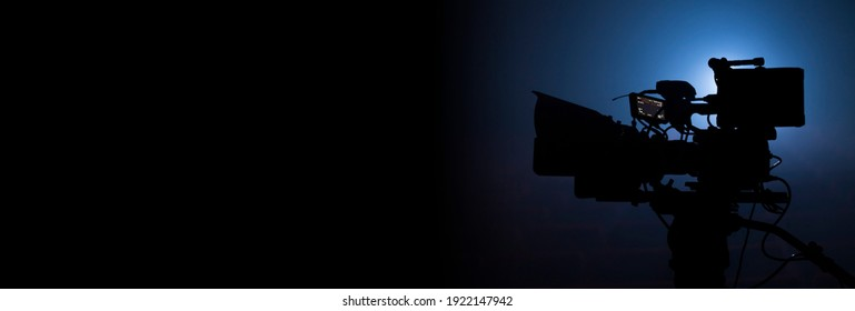 Professional video camera silhouette in the dark with blue light, movie production or television background banner with copy space