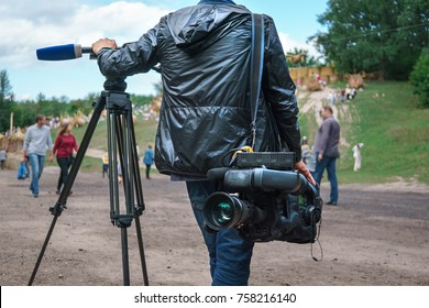 Professional video operator or videographer or cameraman standing with tripod and digital camera at blurred background of park with walking people, view from back, selective focus