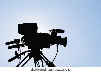 Professional video recording by professional photographers who set up a video camera on the tripod and ready to broadcast the wedding ceremony in open space on the bright sky background of Thailand.