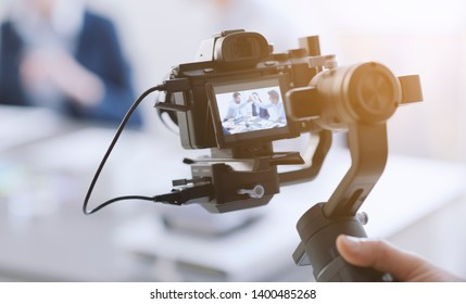 Professional videomaker shooting a video, defocused actors in the background, videomaking and communication concept