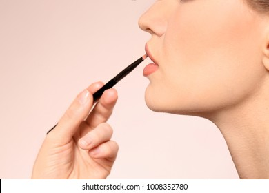 Professional visage artist applying makeup on woman's face on light background