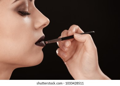 Professional visage artist applying makeup on woman's face against black background