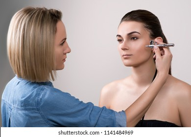 Professional visagist doing makeup and using airbrush. Girl doing makeup in beauty salon. Fashion brunette model with hair tail over gray background. Makeup artist using airbrush