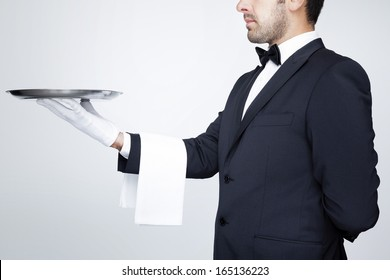 Professional waiter holding an empty silver tray over gray background