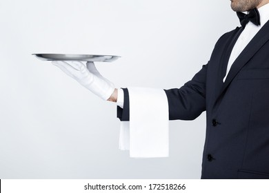 Professional waiter holding empty silver tray over gray background
