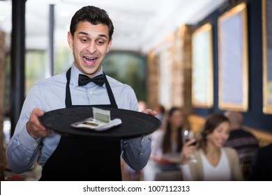 Professional waiter holding serving tray in restaurant with tips