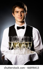 professional waiter in uniform is serving wine (focus on glasses)