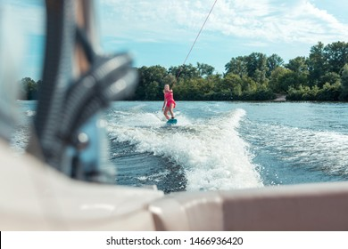 Professional wakeboarder. Confident fit professional female wakeboarder riding a wakeboard while holding on to a rope handle with one hand