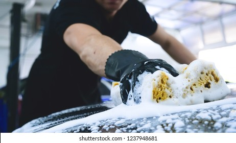 Professional washes the car in black gloves, with a sponge and foam. Concept: Carwash, Sponge, Foam, Water, Professional, Work.