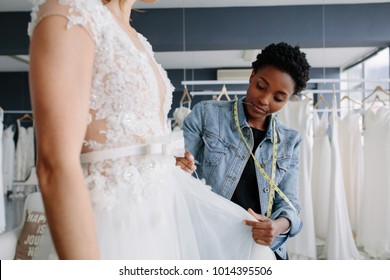 Professional wedding dress designer fitting bridal gown to woman in her store. Woman making adjustments to bridal gown in her boutique.