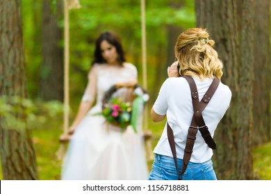 Professional wedding photographer taking close-up portraits of the bride on a rope swing with rustic style bridal bouquet