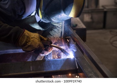 Professional welder in a factory welding steel bars.