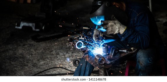 professional welder man working in protect uniform and helmet in industrial factory ,  manufacture linking and repair concept cover background .