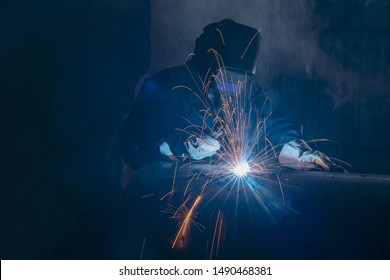 Professional welder and mask welding metal pipe on the industrial table.
