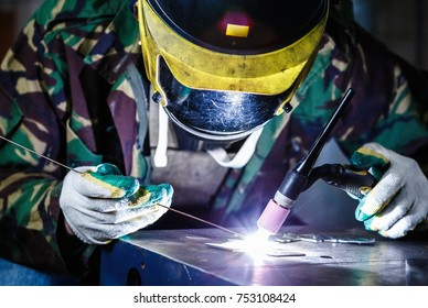 Professional welder in mask welds steel with electric torch tool.Factory worker welding metal parts with burner electrode.Manual labor specialist at metal shop.Bright electric torch burns iron piece