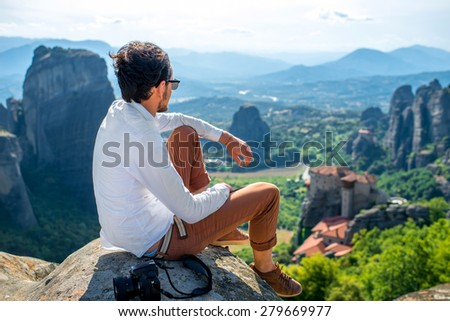 Professional well-dressed photographer sitting on the top of mountain on beautiful scenic clif background near Meteora monasteries in Greece