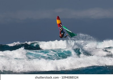 Professional windsurfer riding waves at sunny windy day in the Atlantic ocean. Windsurfing Canary Isalnds, Tenerife, La Caleta