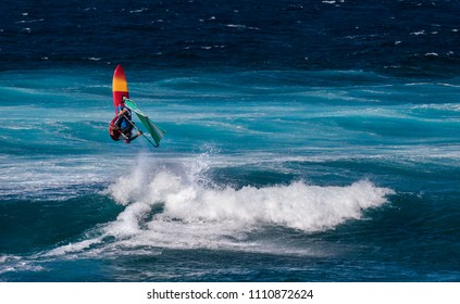 Professional windsurfer riding waves at sunny windy day in the Atlantic ocean. Windsurfing, extreme sport. Canary Isalnds, Tenerife, La Caleta