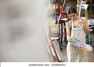 Professional Woman artist painting picture in art studio.
