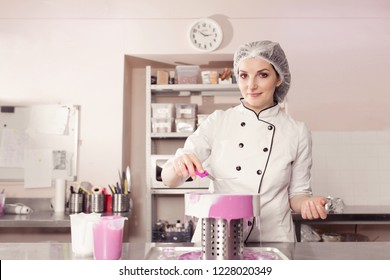 professional woman chef decorating delicious cake with cream and glaze. kitchen portrait