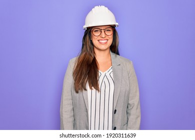 Professional woman engineer wearing industrial safety helmet over pruple background with a happy and cool smile on face. Lucky person.