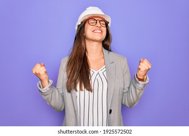 Professional woman engineer wearing industrial safety helmet over pruple background very happy and excited doing winner gesture with arms raised, smiling and screaming for success. Celebration concept