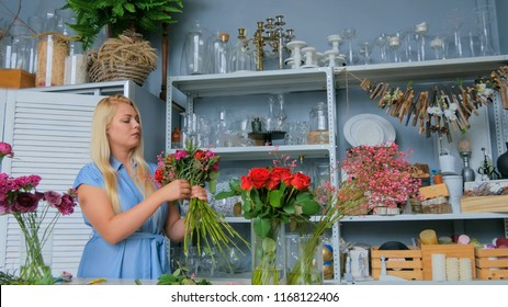 Professional woman floral artist, florist in blue dress making beautiful wedding bouquet at workshop, flower shop. Floristry, handmade and small business concept