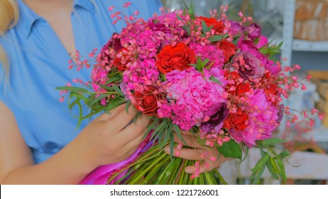 Professional woman floral artist, florist holding and checking beautiful wedding bouquet at workshop, flower shop. Floristry, handmade and small business concept
