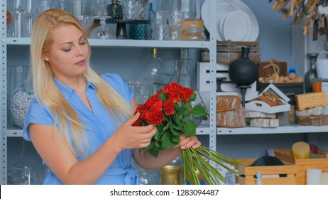 Professional woman floral artist, florist in blue dress making bunch of red roses at workshop, flower shop. Floristry, handmade and small business concept